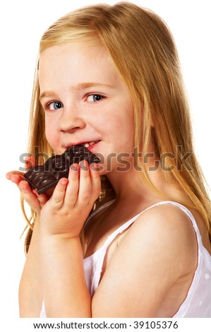 happy little girl eating chocolate; closeup - stock photo