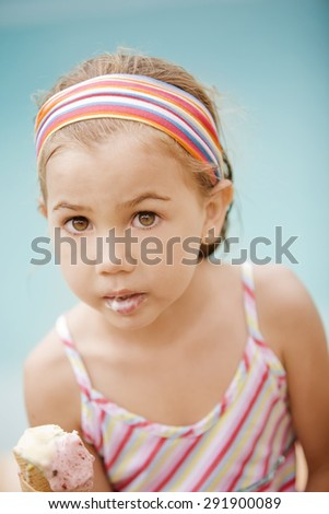 Happy little girl eating ice cream by poolside - stock photo