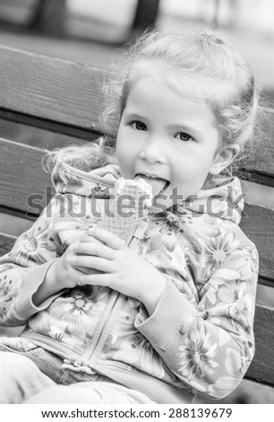 happy little girl eating ice cream outdoors  (black and white) - stock photo
