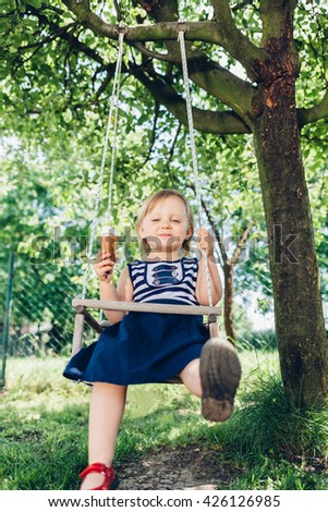 Happy little girl eating ice cream while on the swing - stock photo
