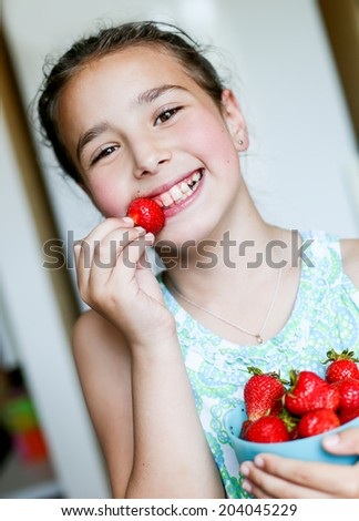 happy little girl eating strawberries at home - stock photo