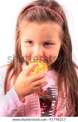 Happy little girl eating tasty doughnut