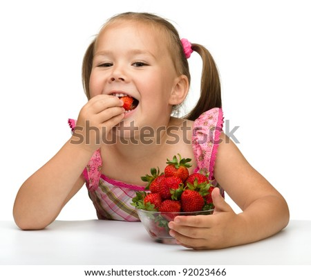 Happy little girl eats strawberries, isolated over white - stock photo