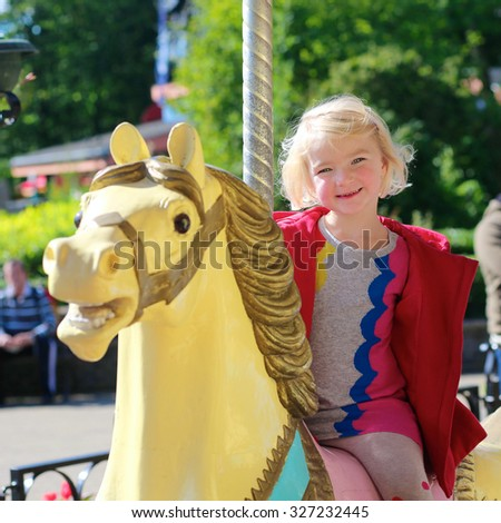 Happy little girl enjoying a ride on the merry-go-round. Cute toddler kid having fun at funfair. Family with kids spending day in amusement park - stock photo