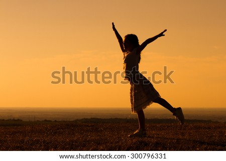 Happy little girl enjoys outdoor.Silhouette of happy little girl - stock photo