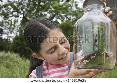 Happy little girl examining stick insects in jar outdoors