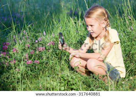 Happy little girl exploring nature with magnifying glass at the day time - stock photo