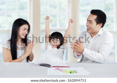 Happy little girl finishing her homework and get applause from her parents at home - stock photo