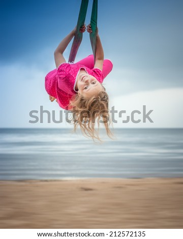 happy little girl flying over the blue sky - stock photo