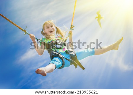 happy little girl flying over the blue sky - stock photo