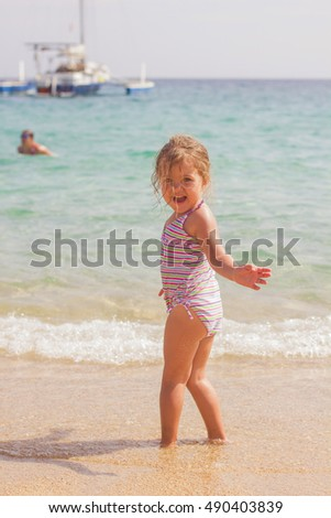 Happy Little Girl fun on the sandy beach. Summer vacation.