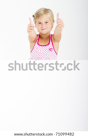 happy little girl giving thumbs up behind white board