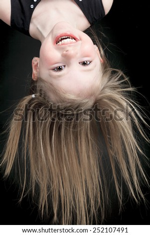 Happy little girl hanging upside down isolated on white - stock photo