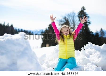 Happy little girl has fun with  snow outdoors