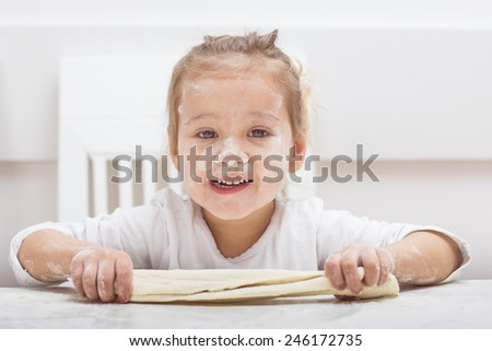Happy little girl have fun with kneading dough at home. - stock photo