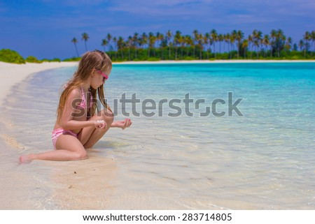 Happy little girl having fun at shallow water at tropical beach