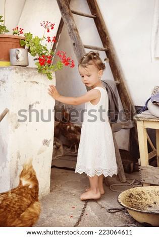 Happy little girl having fun in garden near the old farmhouse - stock photo