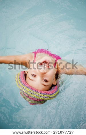 Happy little girl having fun in swimming pool - stock photo