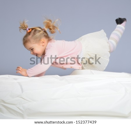 Happy little girl having fun on bed isolated on grey  - stock photo