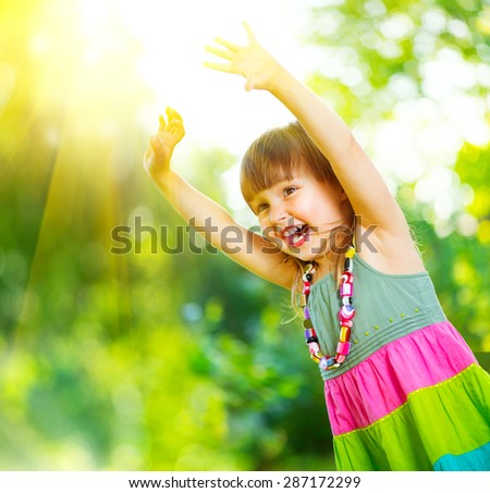 Happy Little Girl Having Fun outdoors. Beautiful Healthy three years old Child Laughing and raising hands, Playing and smiling in summer park. - stock photo