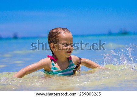 Happy little girl having fun, swimming and jumping at shallow water - stock photo