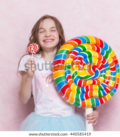 happy little girl hold huge lollipop and small one - stock photo