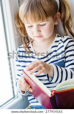 happy little girl holding a book while sitting on the window - stock photo