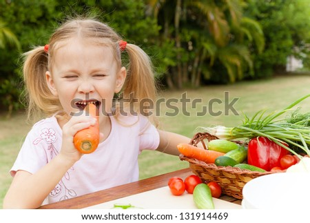 Happy little girl holding a carrots. Concept of healthy food.