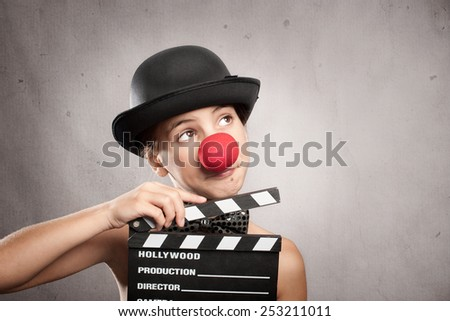 happy little girl holding a movie clapper board on a grey background