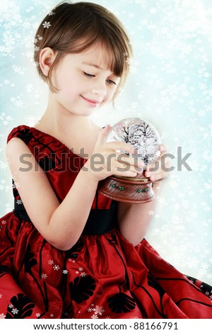 Happy little girl holding a snow globe. - stock photo