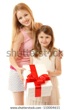 happy little girl holding christmas present with her sister, isolated on white background