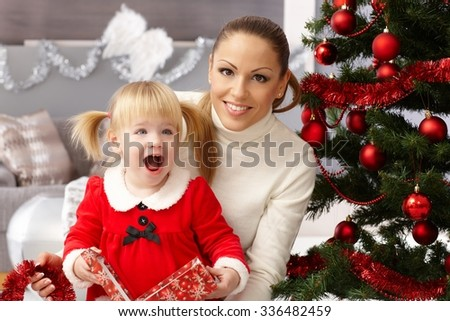 Happy little girl holding christmas surprise sitting by christmas tree with mother.