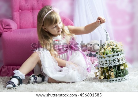 happy little girl holding decorative bird cage full of flowers. Studio shot in provence style interior - stock photo