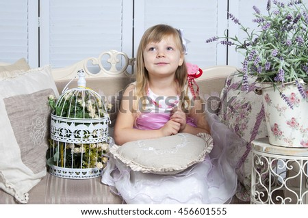 happy little girl holding decorative hearts. Studio shot in provence style interior - stock photo