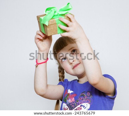 Happy little girl holding  gift box - stock photo