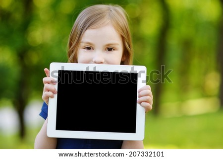 Happy little girl holding tablet PC outdoors in summer park on beautiful sunny day - stock photo