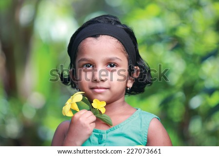 Happy little girl holding yellow flowers in outdoor - stock photo