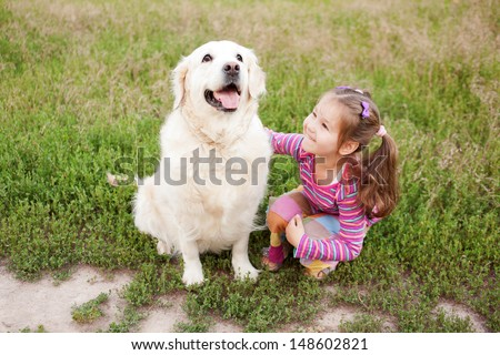 Happy little girl hugging a dog breed golden retriever on green grass in an urban neighborhood. Healthy lifestyles concept. - stock photo