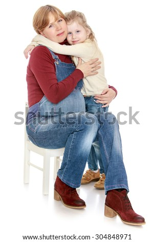 Happy little girl hugging her favorite pregnant mother who is sitting on a chair-Isolated on white background