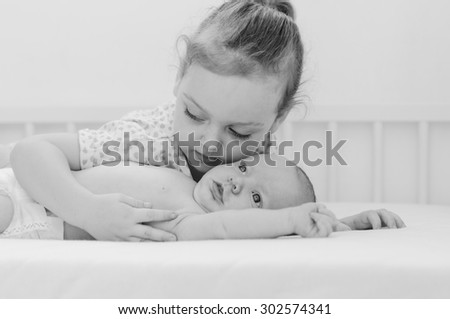Happy little girl hugging her newborn brother - stock photo