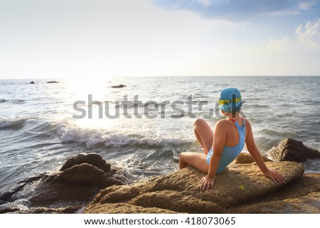 Happy little girl in a bathing suit, swim cap, goggles at the beach - stock photo