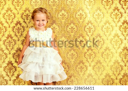 Happy little girl in a beautiful white dress standing by the vintage wall. Childhood. Holiday, birthday. - stock photo