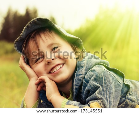 Happy little girl in a hat on a background of nature.
