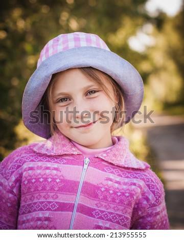 Happy little girl in a hat outside. - stock photo