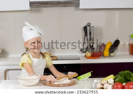 Happy little girl in a white chefs hat making pizza in the kitchen rolling out the dough for the base with a cheerful smile