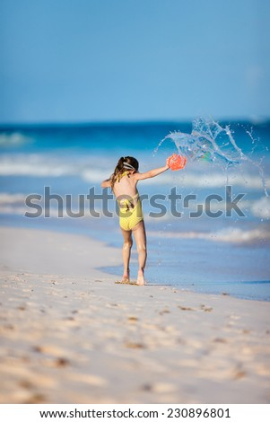 Happy little girl in a yellow swimsuit at a beach playing while having summer vacation - stock photo
