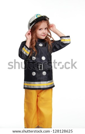 Happy little girl in fireman costume on white background on Holiday