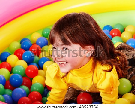 Happy little girl in group colorful ball. - stock photo