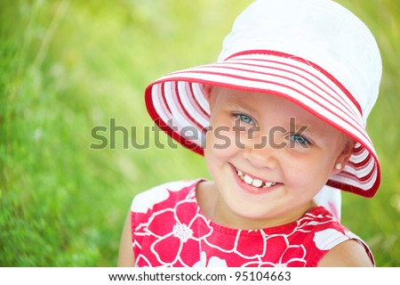 happy little girl in  hat smiling  backgroung green grass - stock photo
