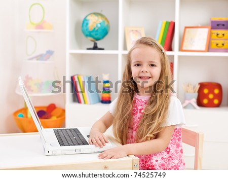 Happy little girl in her room working on laptop computer smiling - stock photo